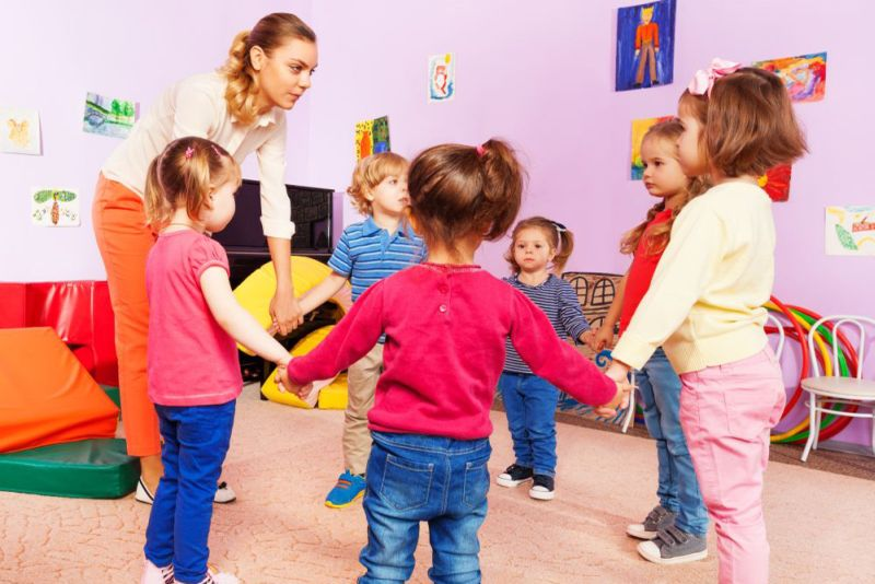 Teacher and group of kids in kindergarten