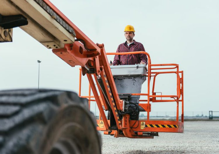 Worker operating Straight Boom Lift